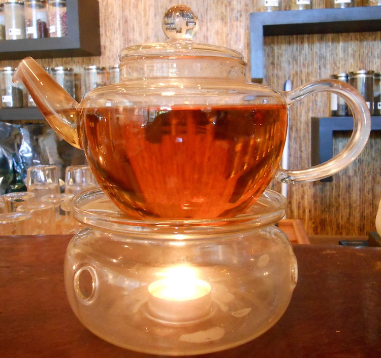 a glass pot of tea on a warmer